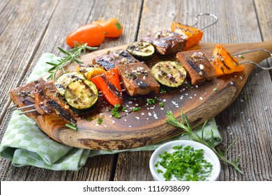 Vegan meal: Grilled skewers with mixed vegetables and seitan served  on a wooden cutting board with a herb soy sauce