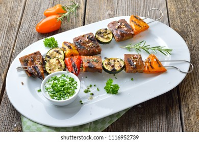 Vegan meal: Grilled skewers with mixed vegetables and seitan served  on a white plate with a herb soy sauce