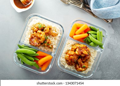 Vegan meal prep with bbq cauliflower with rice, carrots and sugar peas overhead shot