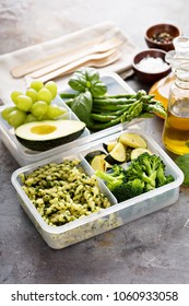 Vegan meal prep containers with pasta with green pesto sauce and vegetables