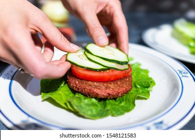Vegan meat sausage patty on plate with romaine lettuce leaf and tomatoes cucumbers sliced for burger with female hand arranging dish