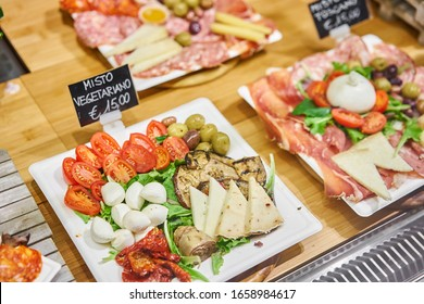 vegan menu. Light Italian snacks. Cheese plate with tomatoes and olives. Delicious cheese mix on wooden plate. Street food market in Florence, Italy.