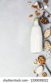 Vegan milk and ingredients on rustic background, flat lay