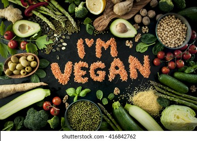 I'm vegan motto with a nice colorful frame made of vegetables and fruits on the black board. Perfect for wallpaper or poster.