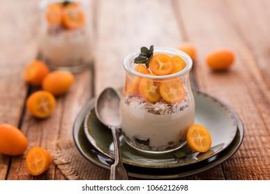 Vegan musli cheescake with cumquat in a jar