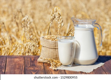 vegan oat milk in glass and jug with sack of grains on table over against ripe cereal field