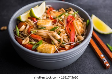 Vegan pad tai with tofu in a blue plate on a dark background with Chinese chopsticks