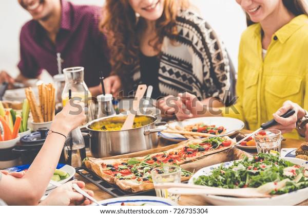Vegan parti, genç arkadaşlar birlikte yeni vegan tarifleri deniyor, sohbet ediyor ve renkli görkemli yemeklerle dolu ortak masada eğleniyor