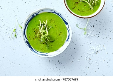 Vegan Pea Soup with pea sprouts, lime, black pepper and olive oil (from above). Flat lay. Healthy diet concept. Homemade food. Vegan diet. Bright stone background. Top view.