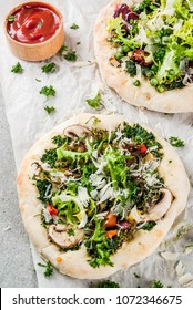 Vegan pizza with fresh vegetables and pesto, gray stone background, copy space