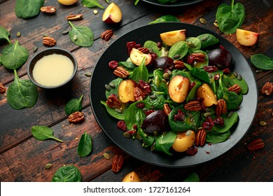 Vegan plums salad with cranberry, pumpkin seed, pecans nuts, spinach and mustard dressing