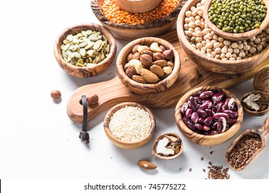 Vegan protein source. Legumes - lentils, chickpeas, beans, green mung bean, seeds and nuts on white background.