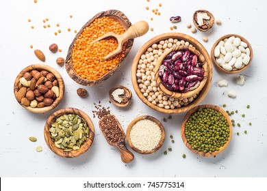 Vegan protein source. Legumes - lentils, chickpeas, beans, green mung bean, seeds and nuts on white background. Top view.