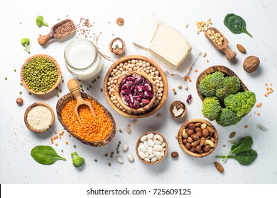 Vegan protein source. Tofu, vegan milk, beans, lentils, nuts, broccoli spinach and seeds. Top view on white table. Healthy vegetarian food.