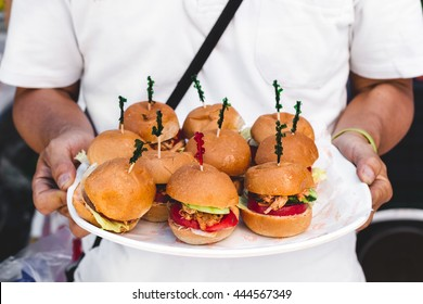 Vegan Pulled Pork Sliders on a Plate Held by a Server at a Vegan Food Festival