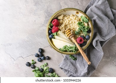 Vegan quinoa porridge with kale, strawberries, blueberries, sliced pear, honey on dipper in bowl with ingredients above and cloth napkin over grey texture background. Top view, space. Healthy eating