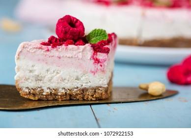 Vegan raw raspberry nut cheesecake on a light  background. Healthy vegan food concept.  Sugar, dairy and gluten free dessert