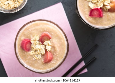 Vegan rhubarb and oatmeal smoothie in glasses, garnished with oats and cooked rhubarb pieces, photographed overhead on slate (Selective Focus, Focus on the top of the smoothies)