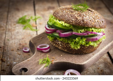 Vegan rye burger with fresh vegetables on rustic background