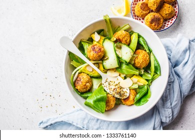 Vegan salad with beans meatballs, avocado and cucumber in white plate on a white background.