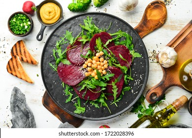 Vegan salad: beets, arugula and chickpeas on a black stone plate. Healthy diet food. Top view. Free space for text.