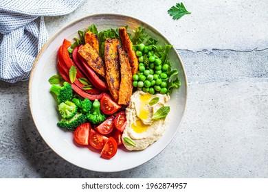 Vegan salad bowl with sweet potatoes, broccoli, tomato, peas and hummus, top view.