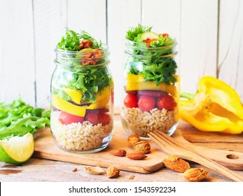 Vegan salad jar with green oak, yellow bell peppers beetroot, cherry tomato, and brown rice on a rustic chopping board for dietary food or light meal concept.