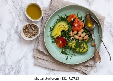 Vegan salad with rucola, seeds, avocado, orange and beans seasoned with olive oil. Healthy eating concept