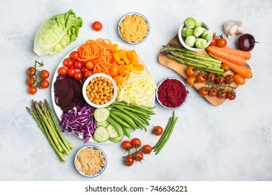 Vegan salad, top view of buddha bowl, colourful vegetables, carrot, courgette, cabbage, chickpeas, cucumber and tomatoes, on wooden board on white table, copy space, top view, selective focus