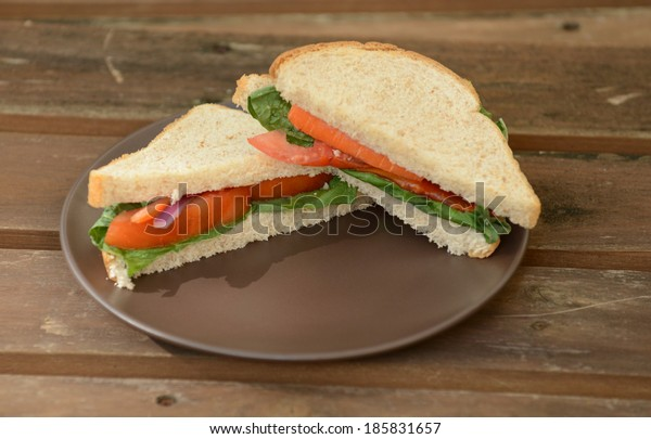 vegan sandwich on wheat bread with tomatoes and lettuce