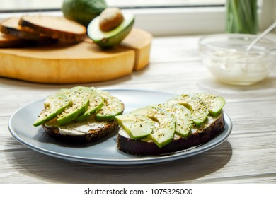 Vegan sandwich, rye bread toast, avocado slices and raw arugula. Toasted sourdough, eggless mayonnaise, wooden table, whole & halved. Vegetarian diet food. Clean eating concept. Close up, background.