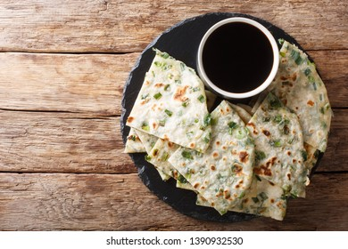 Vegan Scallion Pancakes are a crispy pan-fried Chinese flatbread close-up on a board on the table. horizontal top view from above