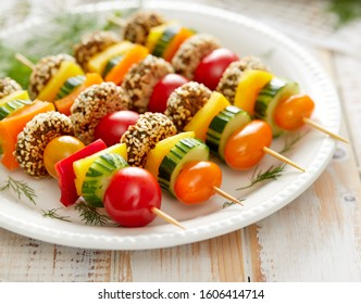 Vegan skewers with falafels and fresh vegetables on a white plate on a wooden white table, close-up. Delicious and healthy appetizer