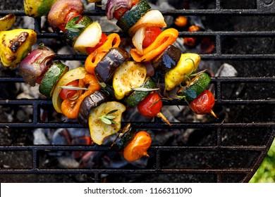 Vegan skewers of various vegetables on the grill plate, top view
