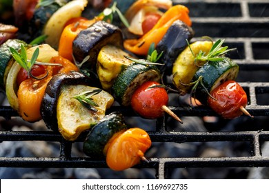 Vegan skewers of various vegetables on the grill plate, top view. Healthy eating concept