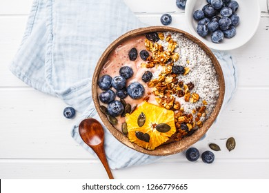 Vegan smoothie bowl with chia pudding, berries and granola in coconut shell on white background, top view, copy space. Plant based diet concept.