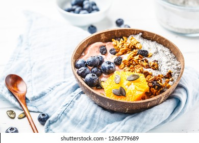 Vegan smoothie bowl with chia pudding, berries and granola in a coconut shell on a white wooden background. Plant based diet concept.