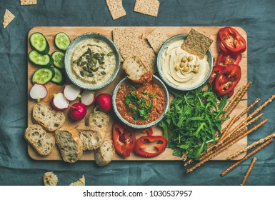 Vegan snack board. Flat-lay of Various Vegetarian dips hummus, babaganush and muhammara with crackers, bread, fresh vegetables on wooden board over grey background. Clean eating, dieting food concept