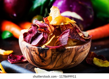 Vegan snacks, multicolored vegetable chips in wooden bowl and set of fresh farmer vegetables, rustic still life, selective focus