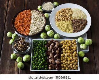 Sources de protéines végétales : grains, lentilles, haricots, noix et choux de Bruxelles sur une table en bois foncé