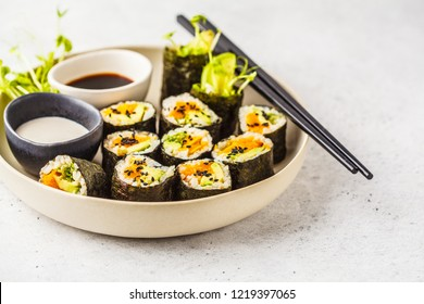 Vegan sushi rolls with pumpkin, brown rice and avocado. Plant based diet food.
