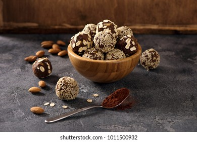 Vegan sweet bites, raw eating homemade dessert with nuts and cacao, sesam and oats