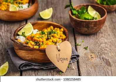 Vegan Sweet Potato Chickpea curry in wooden bowl on a wooden background.