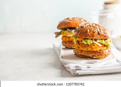 Vegan sweet potato (or pumpkin) burgers on white background. Vegetable burgers, avocado, vegetables and buns. Clean eating, plant based food concept.