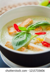 Vegan Thai Green Curry with fried firm tofu pieces, sesonal vegetable, red bird's eye chili and sweet basil.