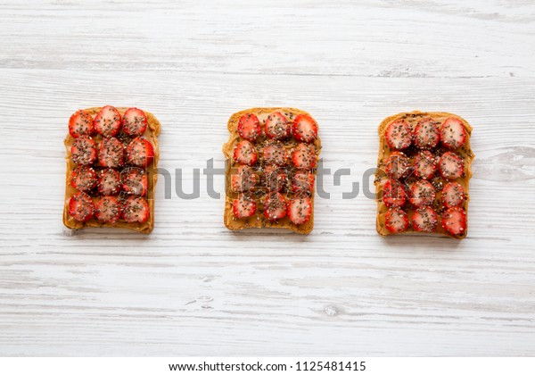 Vegan toasts with peanut butter, strawberries and chia seeds on a white wooden surface, top view. Healthy dieting.