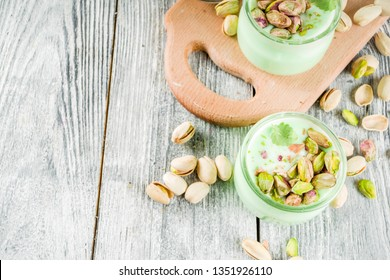 Vegan trend food. Homemade pistachio yogurt with fresh pistachios. On a white wooden table, copy space