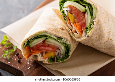 Vegan vegetable wrap with lettuce, cucumber and tomatoes sliced in half