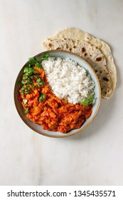 Vegan vegetarian curry with ripe yellow jackfruit served in ceramic bowl with rice, coriander and homemade flatbread flapjack over white marble background. Flat lay, space