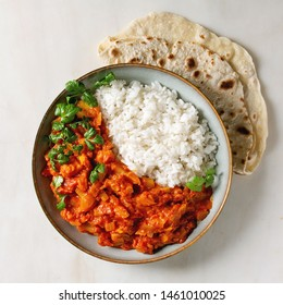 Vegan vegetarian curry with ripe yellow jackfruit served in ceramic bowl with rice, coriander and homemade flatbread flapjack over white marble background. Flat lay, space. Square image